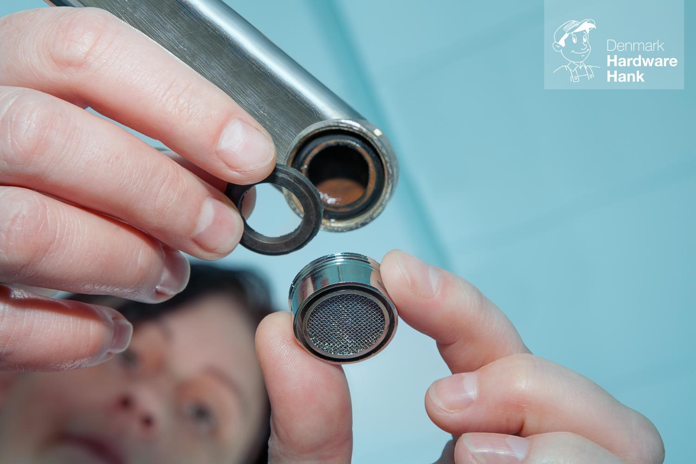 Denmark Hardware Hank Women handyman replace tap aerator, plumber hand close-up.